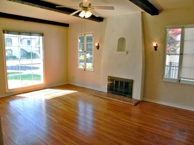 view of living room with beamed ceiling, original hardwood floors, large picture window and fireplace with period alcove accent