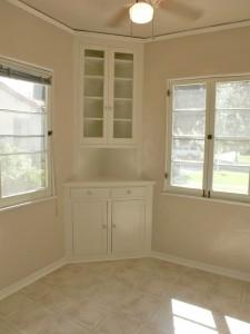 Incredibly charming breakfast nook with corner hutch, ceiling fan, original casement windows and new linoleum flooring!