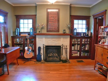 Den off of the living room, with bookshelves flanking the fireplace.  This room can be closed off with the functioning original pocket doors!
