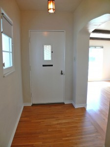 view of hardwood floor entry and step-down living room to the right