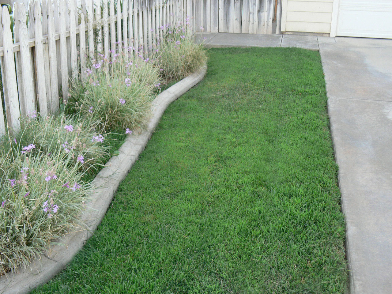 Side yard with hardscaping and white picket fence shows pride of ownership.