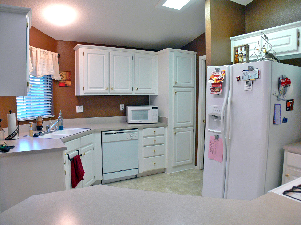 Alternate view of bright and cheery kitchen, with dishwasher, pantry, and doorway into separate laundry room.