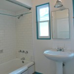 Subway tile tub enclosure and pedestal sink with lots of natural light.