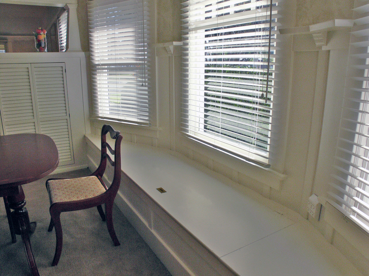 Formal dining room window seat, perfect for hiding the table leaf, linens, and decorations.