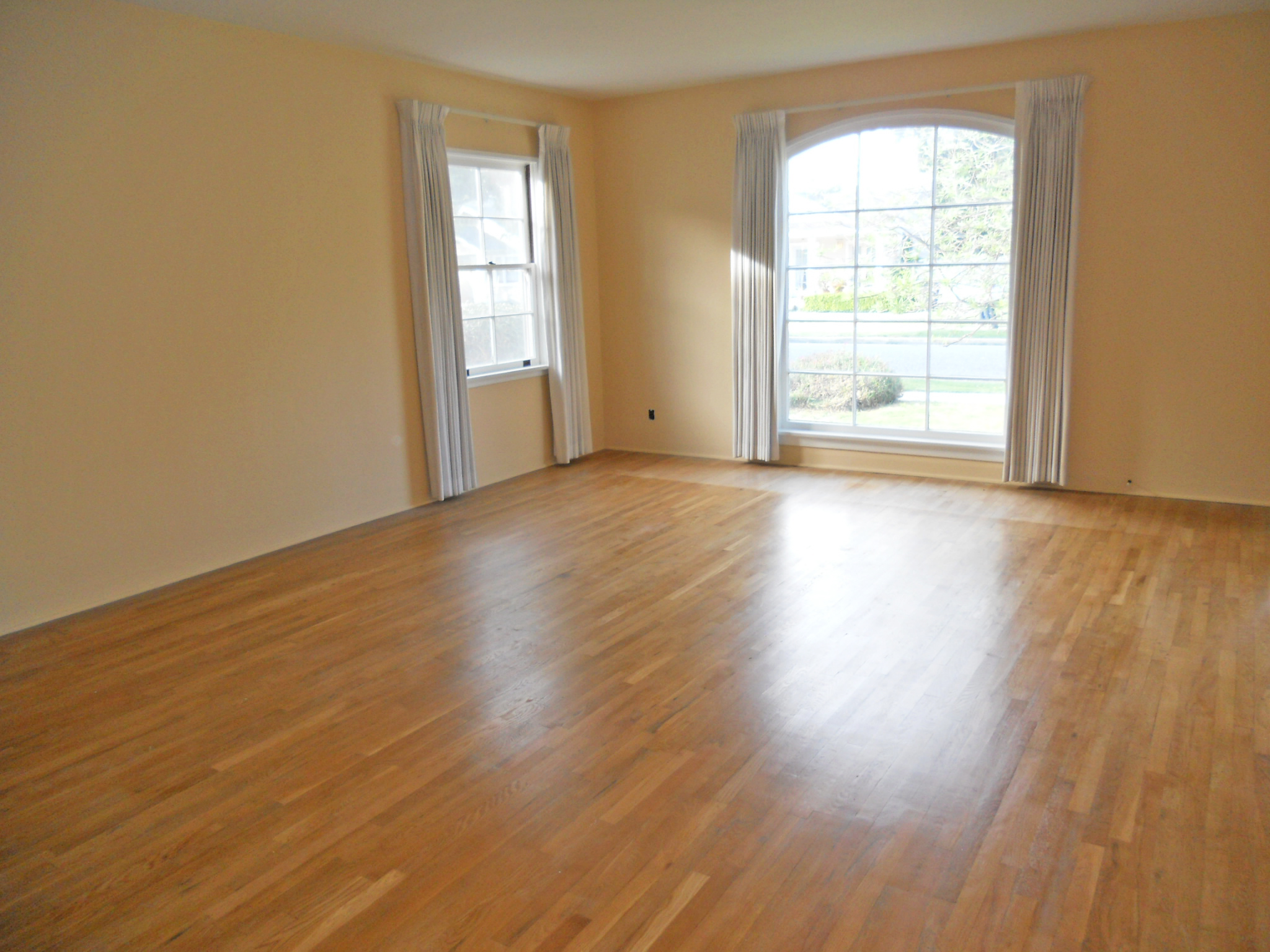 Spacious living room with original hardwood floors and large picture window.
