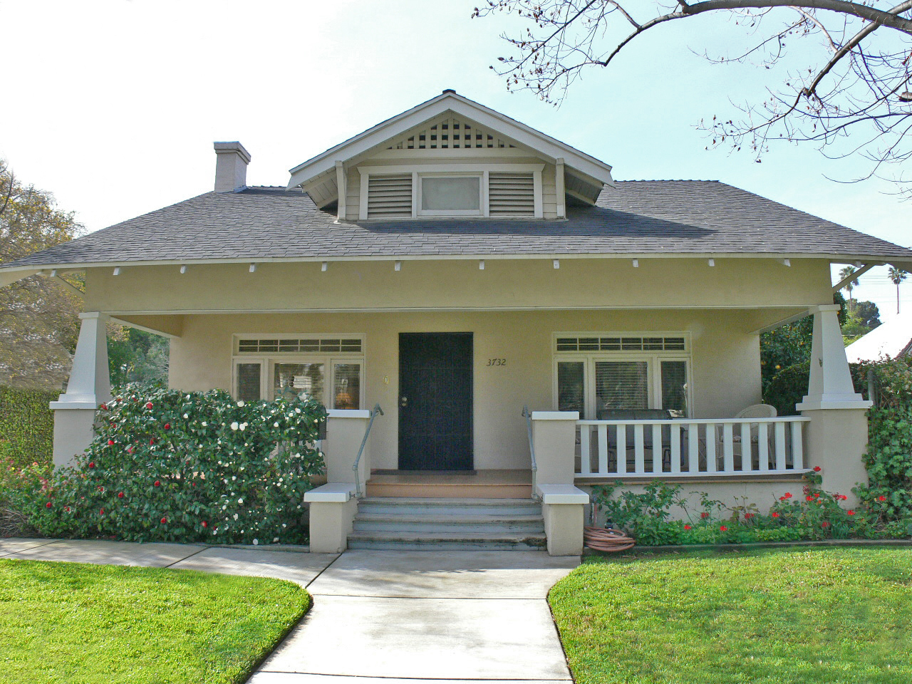 Classic California Bungalow with porch covered by overhanging roof and supported by substantial columns
