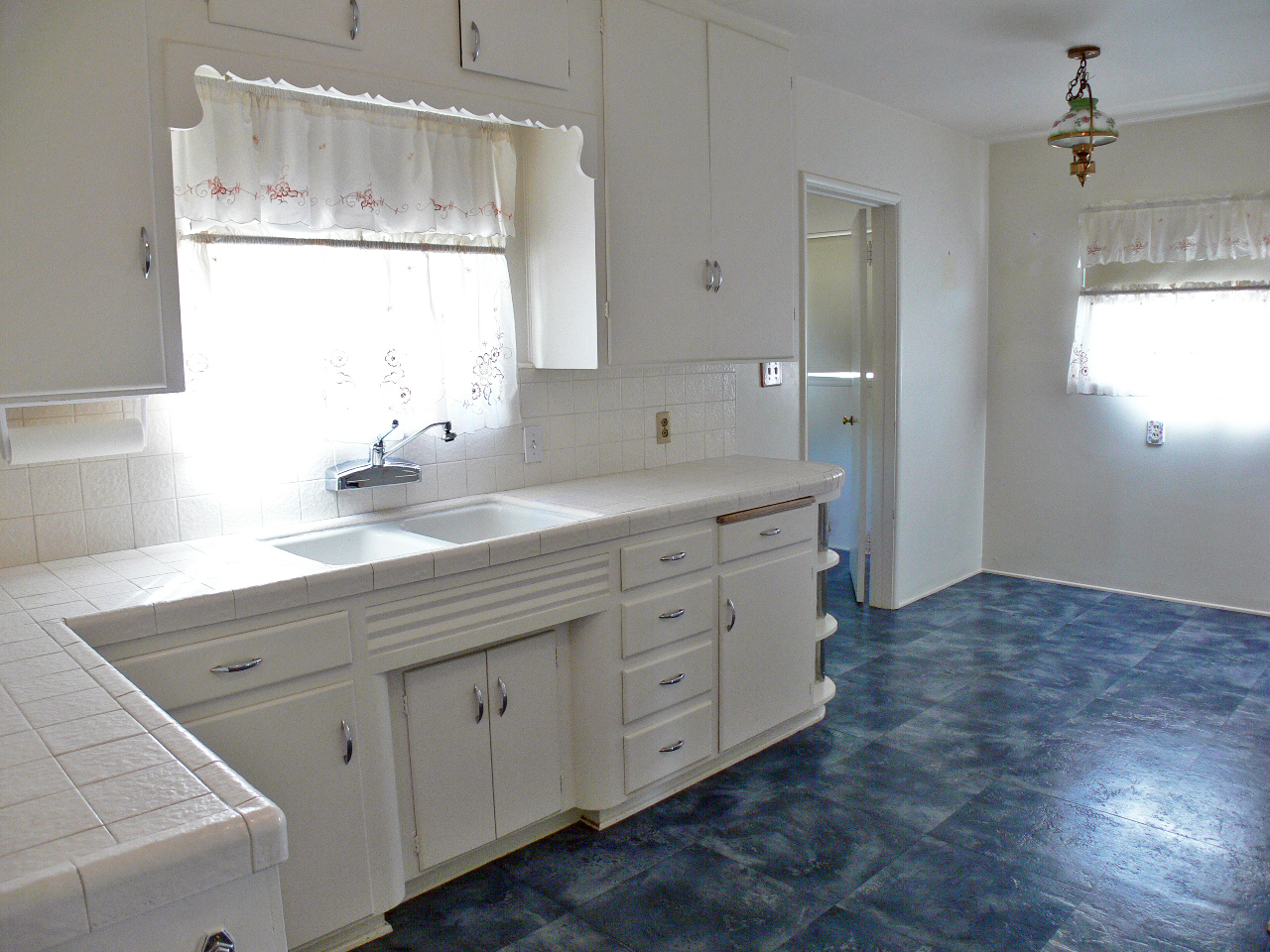 Bright and spacious family kitchen with tile counter top and breakfast nook area.
