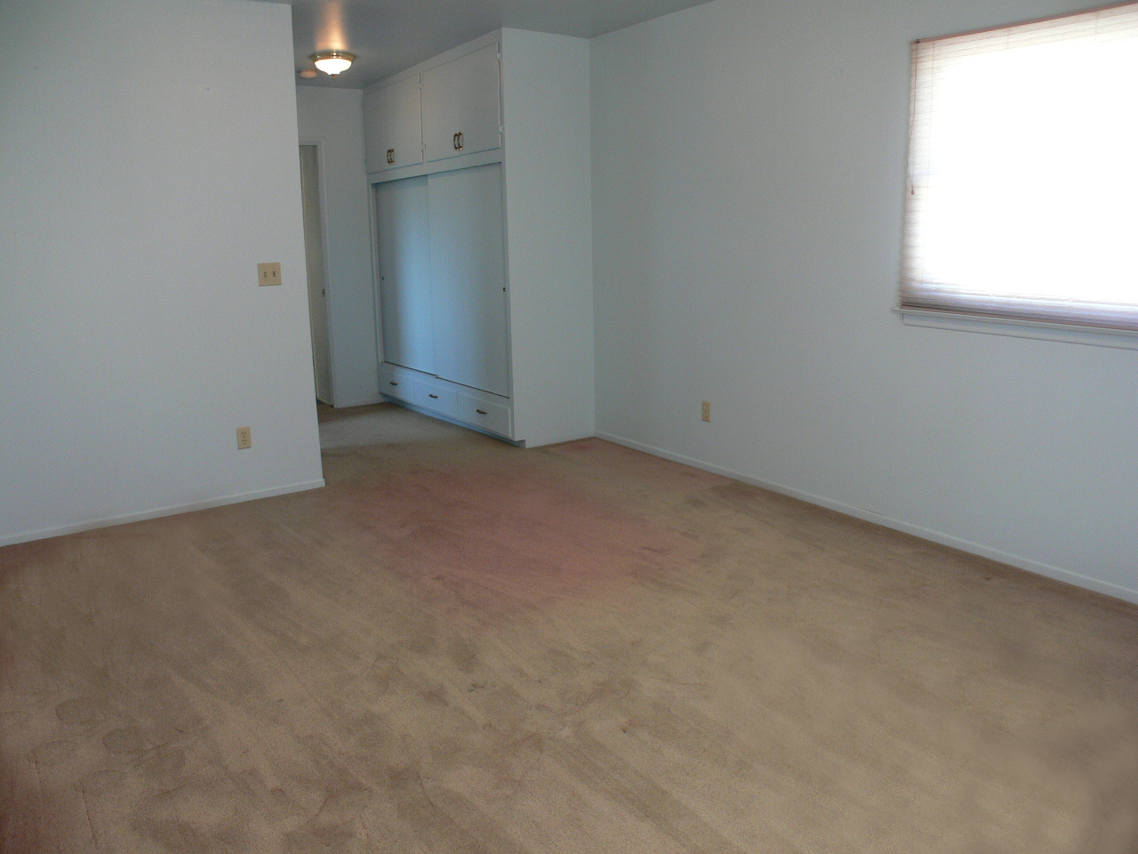 Spacious master bedroom with private 3/4 bathroom and large closet. Carpeting is sun-faded, but we're told there might be hardwood floors underneath!