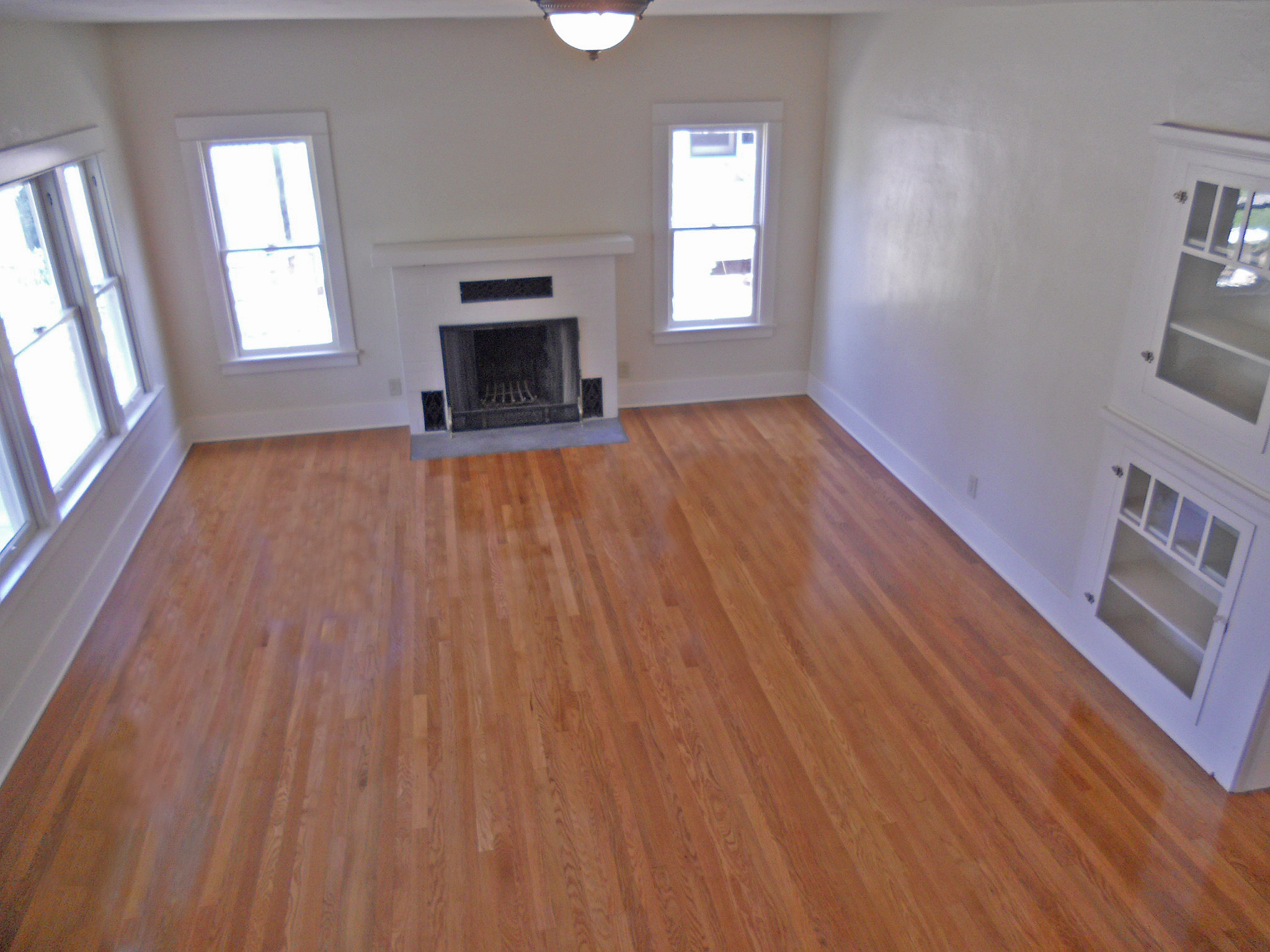 View of large living room with newly refinished original hardwood floors.