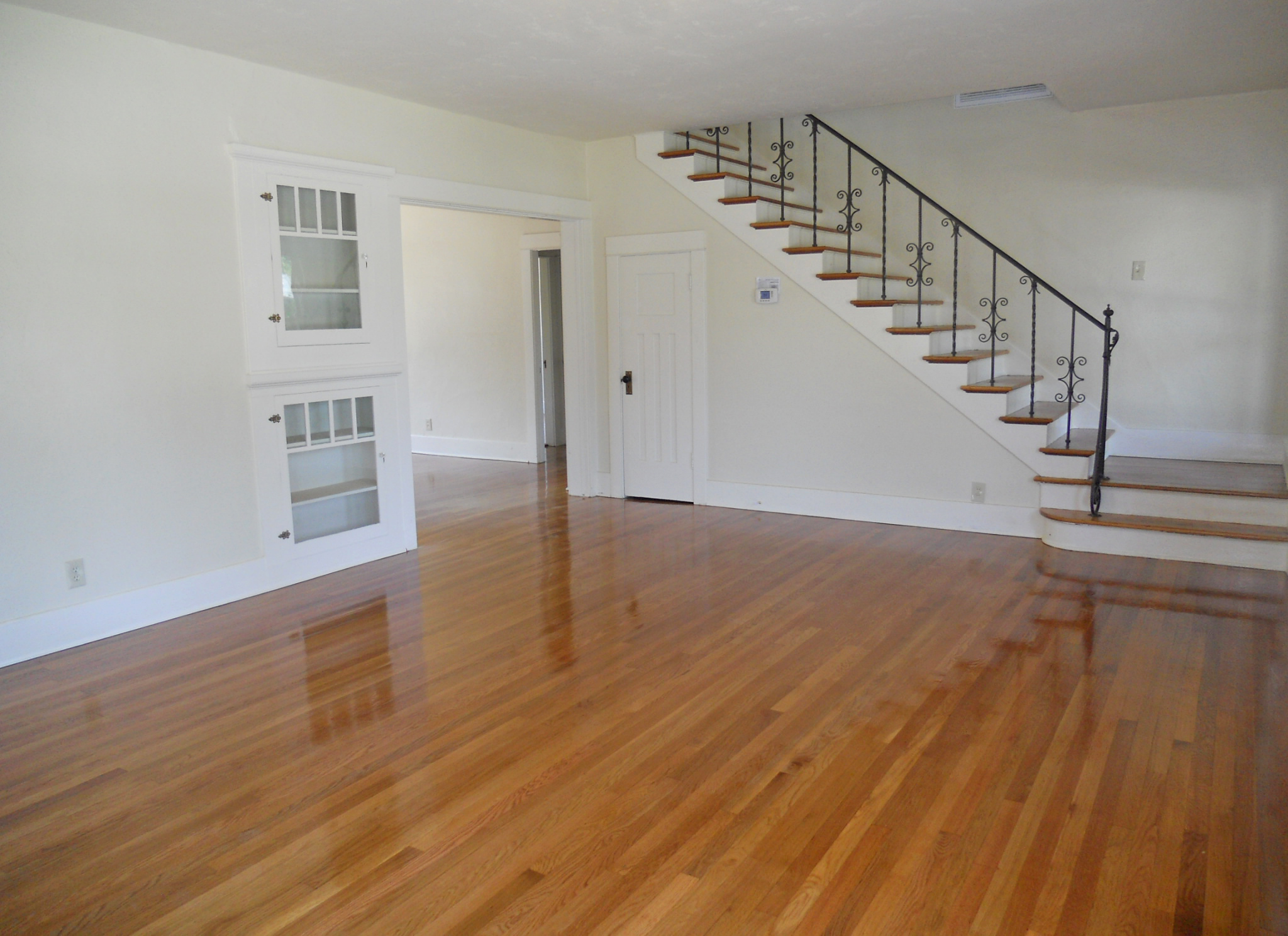 Alternate view of living room with entryway into formal dining room, and original stairway.