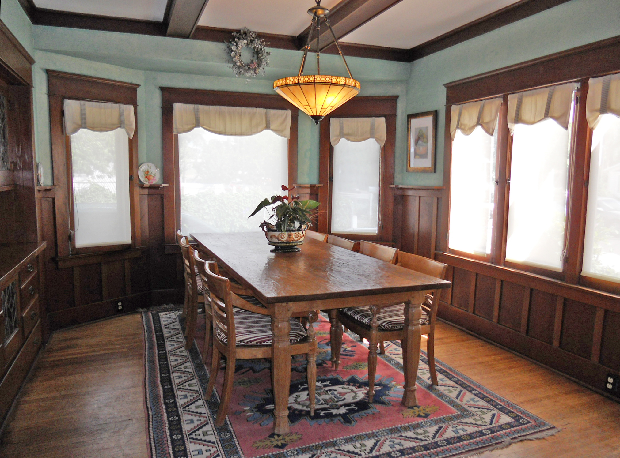 Magnificent formal dining room with wood-beamed ceiling, hardwood floors and plate rails!