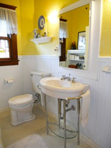 Charming bathroom withy newer pedestal sink, tile floor, stained glass window and soaking tub.