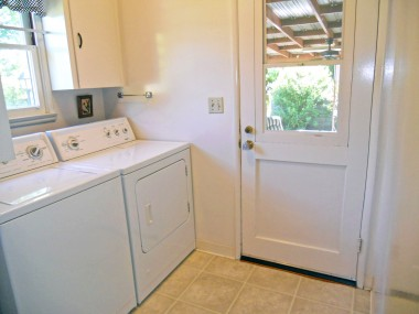 Spacious laundry room with cabinetry and exit door to covered patio.