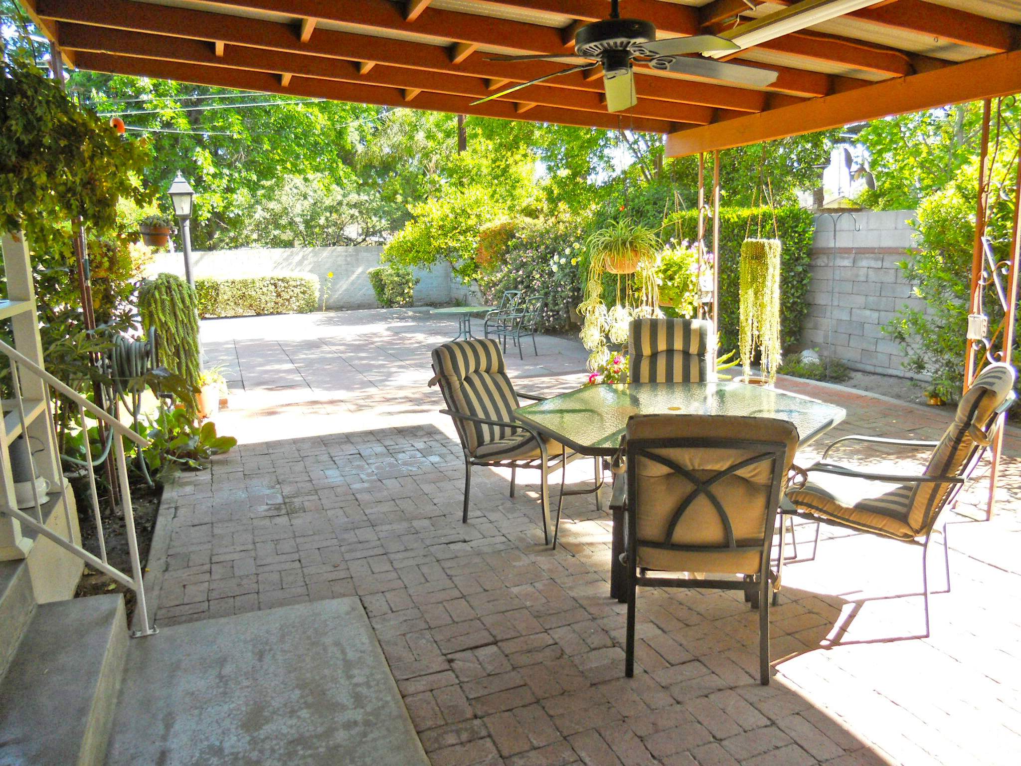 Lovely, breezy covered patio off the side of the house, which makes room in the backyard for a pool.