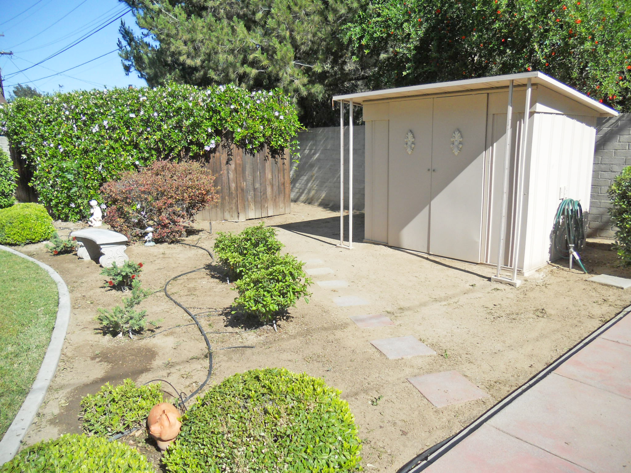 Look how manicured this yard is! Behind the fence with greenery is a huge place to store wood piles, seasonal lawn furniture and lawn equipment.