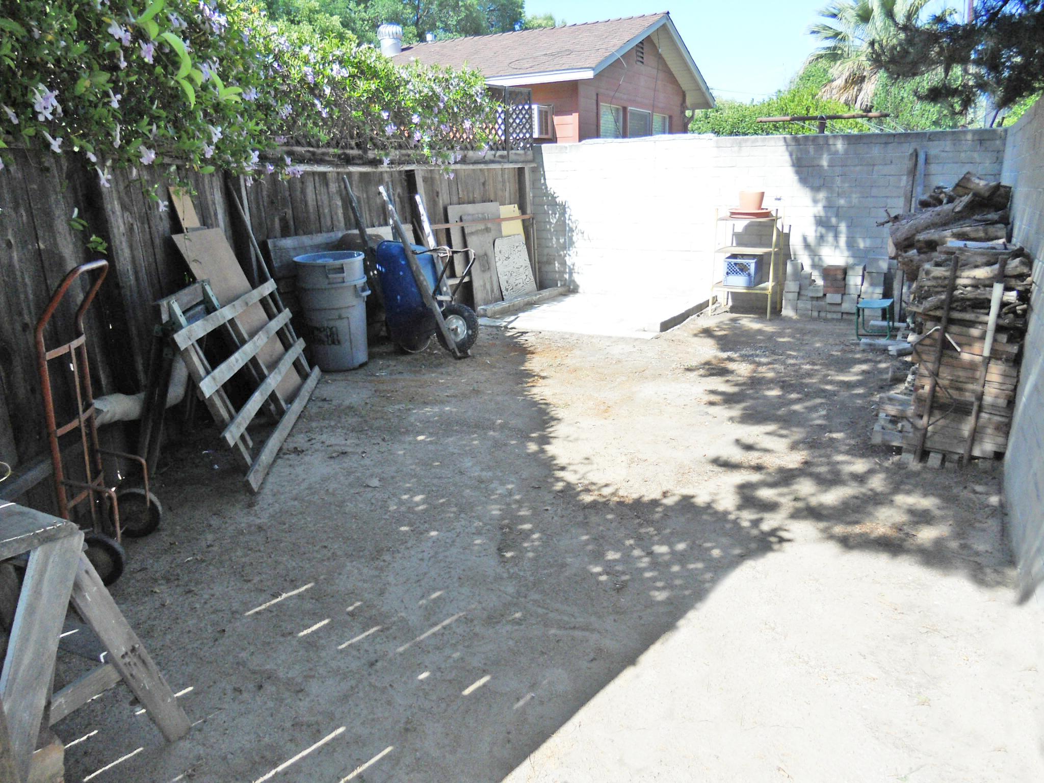 Huge hidden storage area in back corner of yard -- or plant raised-bed gardens!