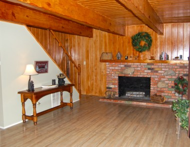 Re-stained wood walls and beamed ceiling. Lots of care went into making this cabin nice and cozy! Gas and wood-burning brick fireplace with mantle!