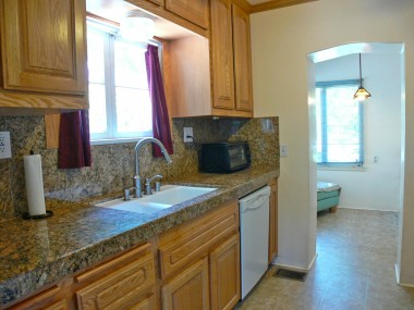 Remodeled kitchen with granite counter tops and dishwasher.