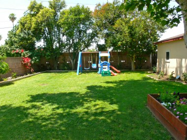 Spacious backyard surrounded by block wall. Sprinklers, garden area, and private shed area behind the 2-car garage!