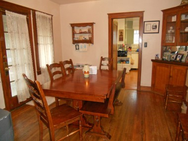 Formal dining room with two built-in corner hutches, hardwood floors and French door to side patio!