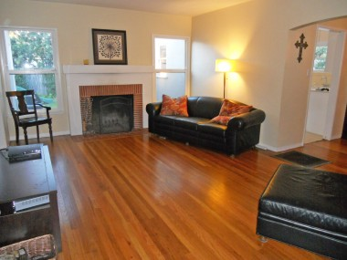 View of living room from front door entry. Note the gorgeous original hardwood floors that have been refinished!