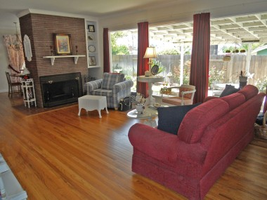 Living room fireplace with built-in shelves and hardwood floors, overlooking the tranquil backyard!