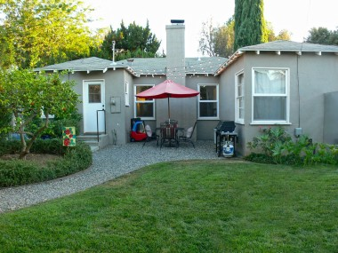"Back of home view. Note the cute patio lights hovering over the patio area for evening gatherings. Citrus trees, a pumpkin patch, and perimeter gardening round out this ""everything-you've-always-wanted-in-a-Wood-Streets"" home!"