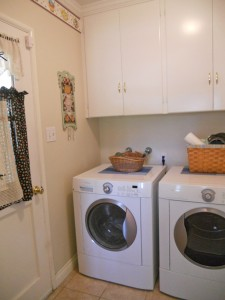 Indoor laundry room with plenty of cabinetry and space for today's modern appliances.
