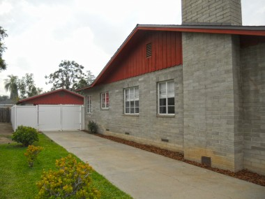 Side of house with driveway leading to vinyl fence and backyard.