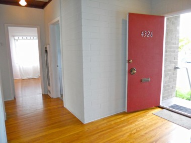 View of front entry and down the hallway to the first of three bedrooms (old wall heater is still intact, but disconnected due to new forced air furnace).