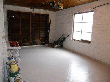 The one-car garage with a linoleum floor, auto garage door opener, large window and wood ceiling.