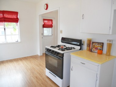 Alternate view of kitchen with original yellow tile counter top.  Access door leads to the expansive backyard.