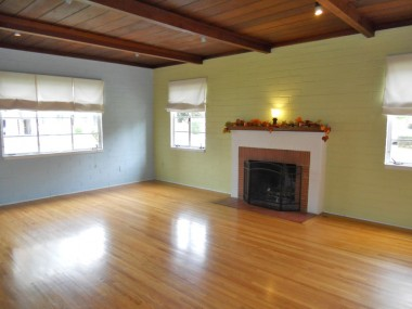 Living room with wood-beamed ceiling, gas and wood-burning fireplace, and gorgeous original hardwood floors.