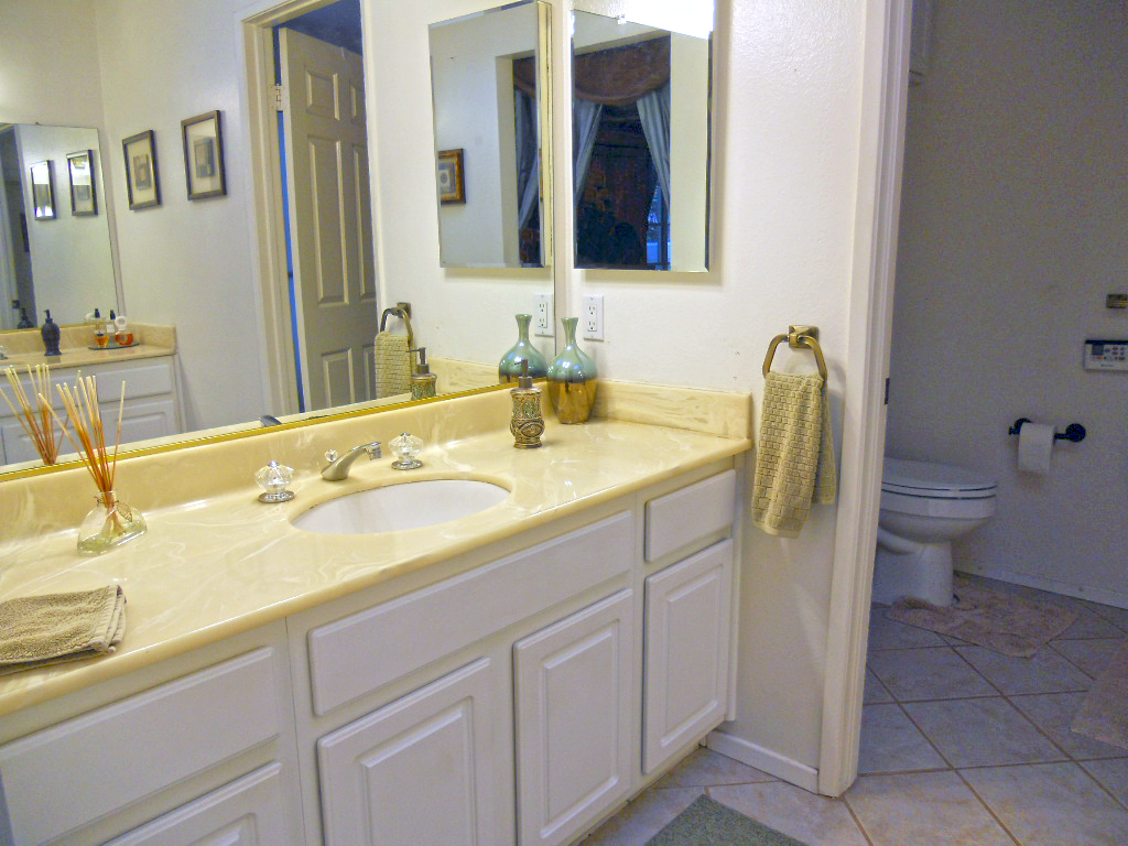Private master bathroom with two vanities, and a separate room with a soaking tub.