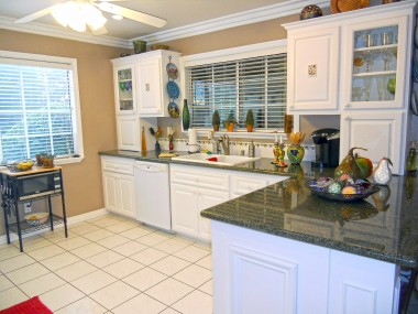 Remodeled kitchen with granite counters, tile floors, dishwasher, and glass-fronted cabinets.