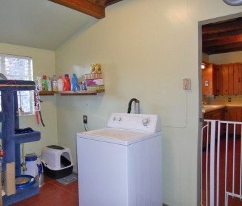 Large indoor laundry room with wood ceiling and plenty of storage.