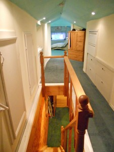 Top of stairway leading to the converted attic space with seemingly unlimited storage space and extra bathroom and bedroom/den area, and reading nook.