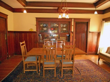 Large formal dining room with gorgeous original hardwood floors, box beam ceiling, built-in China hutch and swinging door to the left that leads to the kitchen.
