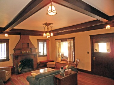 Living room with original hardwood floors, original box beam ceiling with the original light fixtures! Window seats too!