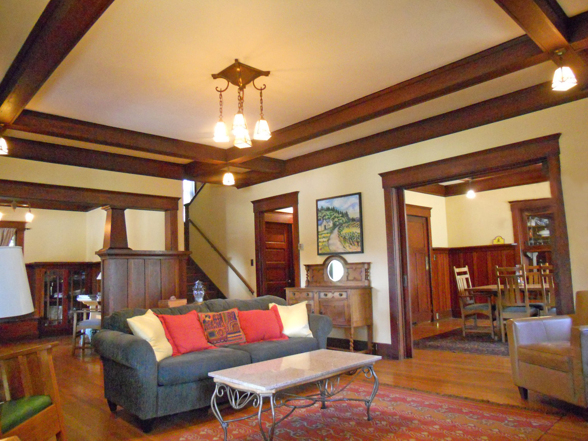 View of formal dining room to the right (through the open pocket doors), stairway to second floor and doorway at bottom of stairs leading to kitchen, and to the far left is the parlor. This is another perfect vantage point to admire the box beam ceiling.
