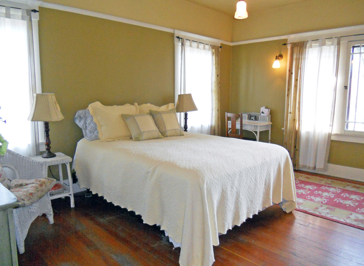 One of four large bedrooms on the second floor. Notice the original wood floors, crown molding and original light fixtures!