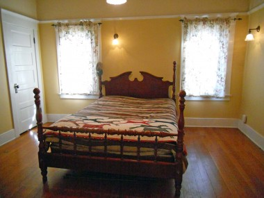 Third of four large upstairs bedrooms with a walk-in closet, original light fixtures and original wood floors.