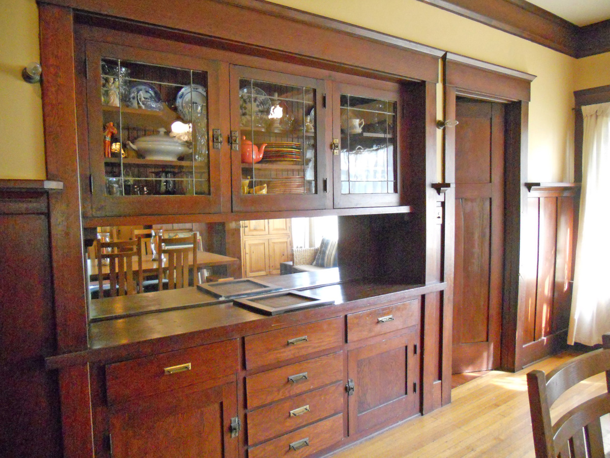 Built-in China hutch with leaded glass and a plate rail that runs the perimeter of the dining room.