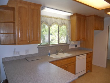 Remodeled kitchen with Corian counter tops, new cabinetry, dishwasher, lazy susan, and breakfast bar in addition to a dining room.