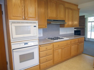 Remodeled kitchen with Corian counter tops, gas cook top, and convenient pull-out drawers.