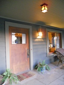 Front door entry with original ceiling light and wood ceiling. Light flanking door is a replica.