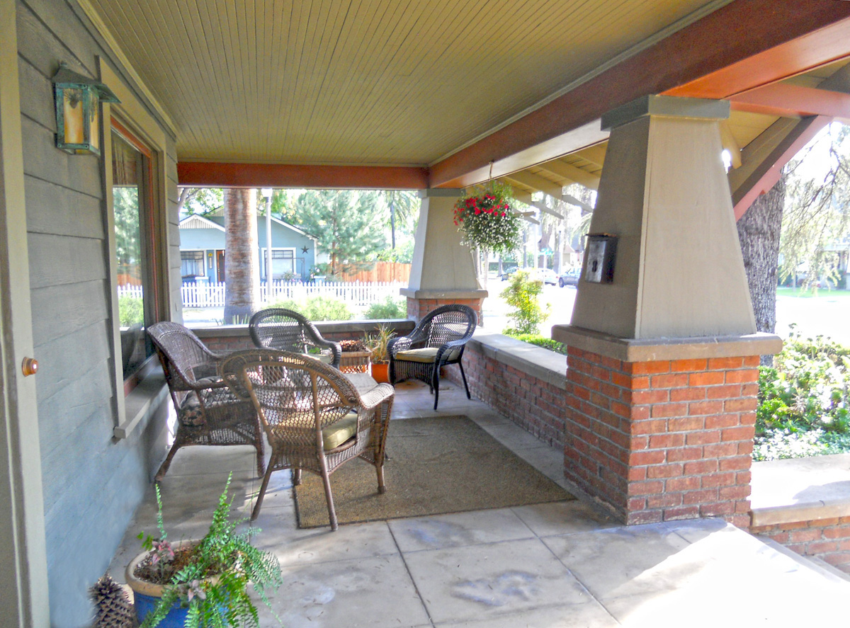 Expansive wraparound front porch with areas for entertaining. Note the wood ceiling and impressive columns.