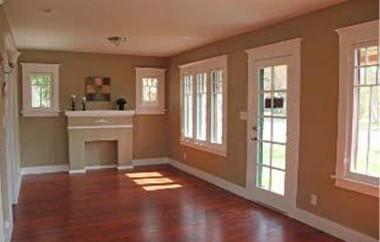 Living room with original faux fireplace, original windows and original front door.