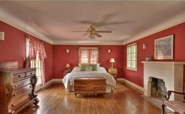 Large master bedroom with fireplace, French doors to private balcony, original hardwood floors and three sets of closets!