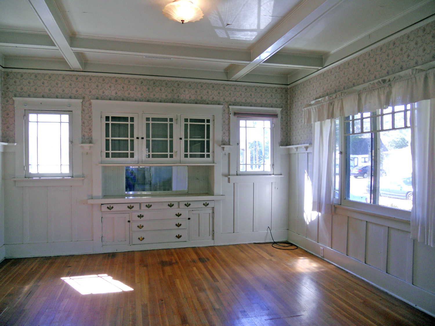 Formal dining room with built-in hutch, plate rails, original hardwood floors, and a box-beam ceiling!!!